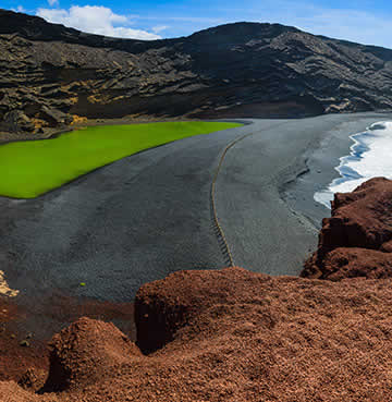 The green, crescent shaped lagoon of Charco de Los Clicos