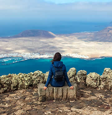 A young woman sits on a rock enjoying the views of Mirador del Rio