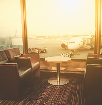 Luxury chairs in an airport lounge, looking out to the runway and planes.