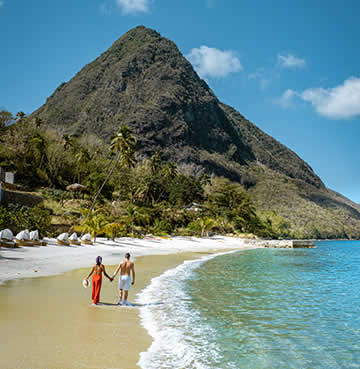 Couple take a romantic walk along Sugar Beach in Soufriere, St. Lucia