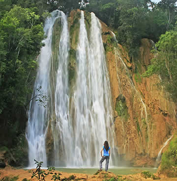 A young woman stands in front of a towering waterfall at a national park in the Dominican Republic