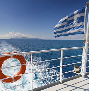 Image showing the side of a Ferry overlooking the sea, with a Greek flag in the foreground.