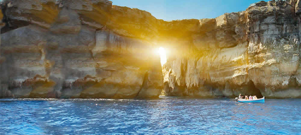 Sun shining through an arch on Gozo's coastline