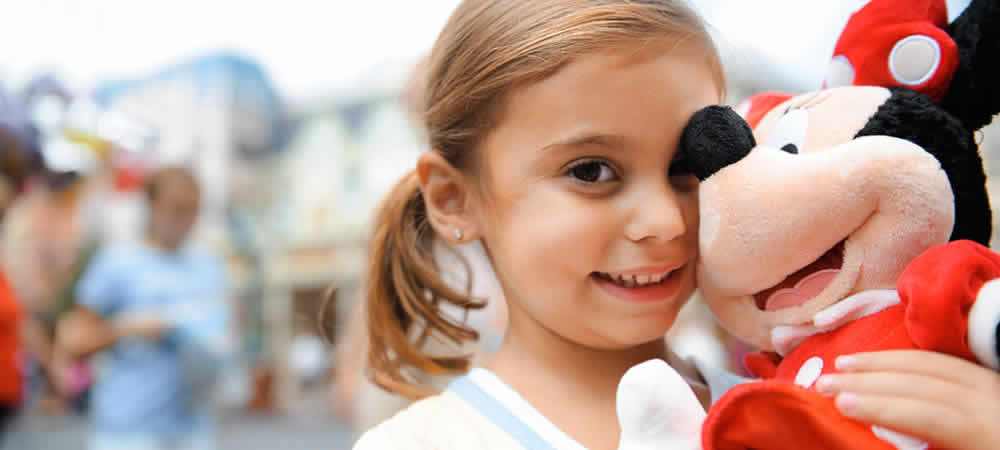 A girl cuddling her Minnie Mouse toy