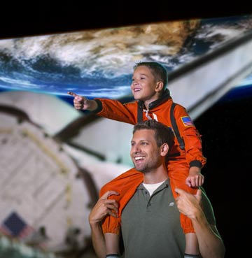 Young boy dressed as an astronaut sitting on a man's shoulders