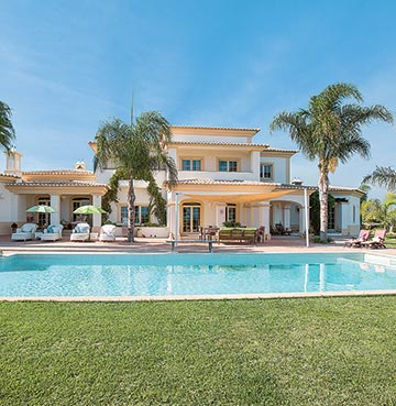 A traditional villa set against perfect blue skies. Palm trees and a large swimming pool sit in the grounds.