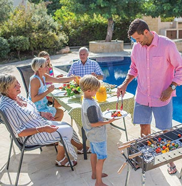 A 3 generation family enjoying a barbecue by their swimming pool at their private villa