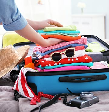 A woman packing her suitcase in a last minute rush. The suitcase is filled with towels, sunglasses and brightly coloured clothes,