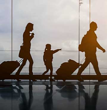Outline of family taking luggage through the airport