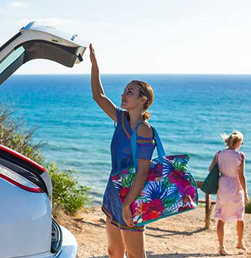 Woman closing the boot of her hire car on villa holiday