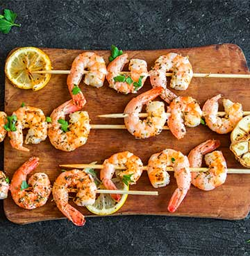 Seafood skewers sitting on a wooden chopping board