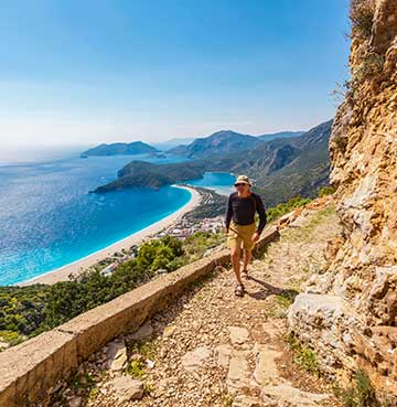 Lone hiker on Turkey's Lycian Way, with stunning Turquoise waters behind