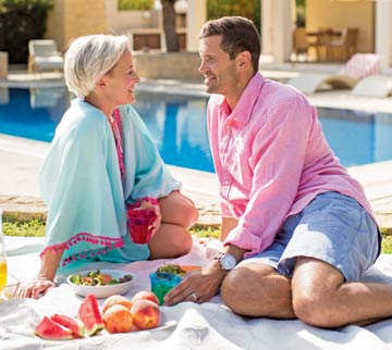 Couple eating a picnic by villa pool