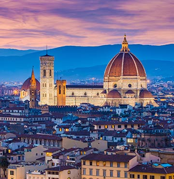 The skyline of Florence, Italy, at night, with the cathedral dome prominent.