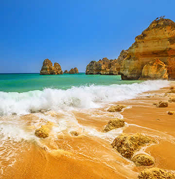 Waves lapping against the golden beach in the Algarve