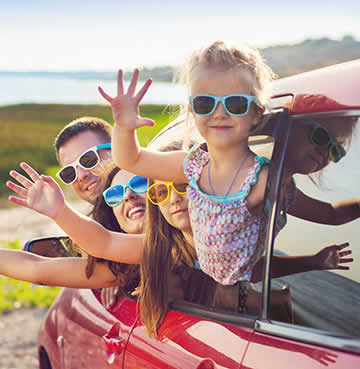 Young family waving at the camera out of the car hire window