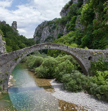 Traditional stone bridge over a river in a verdant valley, Epirus