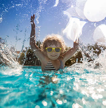 A toddler splashes in a swimming pool
