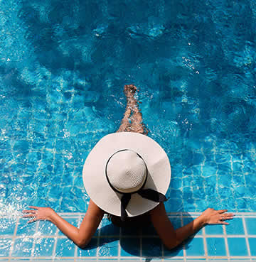 A woman in a sun hat lounging in a swimming pool