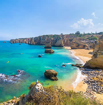 Golden cliffs and sands pop against bright blue skies and aquamarine seas on the Algarve