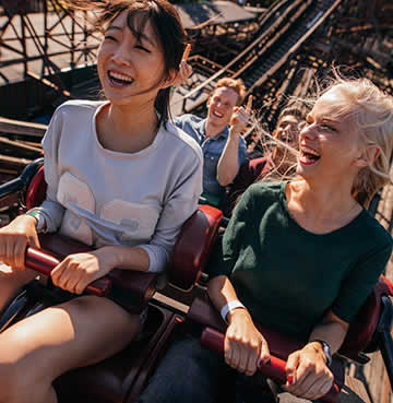 Young friends ride a rollercoaster, laughing and enjoying themselves as they begin the ascent