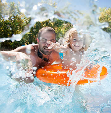 A father and toddler play in a private pool with a bright orange inflatable rubber ring
