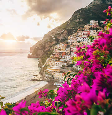 Bright pink Bougainvillea sits in the foreground, with picturesque Positano sitting pretty on the side of a cliff in the background