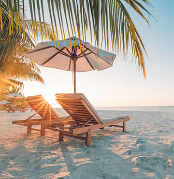 Two sunloungers on a tropical beach at sunset