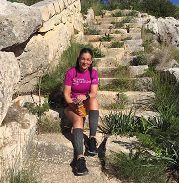A woman in running gear sits on old, stone steps in Malta