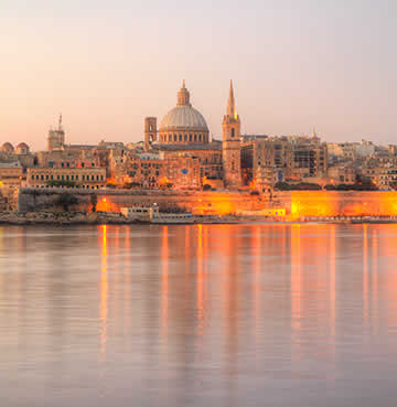 The capital city of Malta, Valletta, as the sun is setting and the city springs to life with splashes of gold lighting.