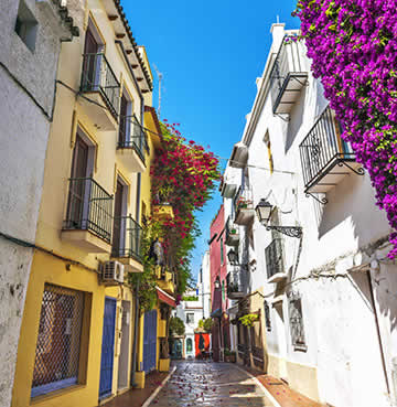 The narrow alleyways of Marbella Old Town, decorated in bright pink bougainvillea and painted in colourful shades.