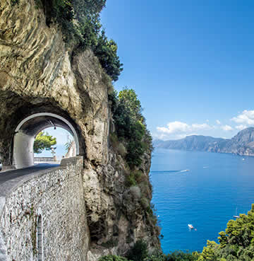 Stunning coastal road along the Amalfi Coast. A tunnel is carved into the cliff face.