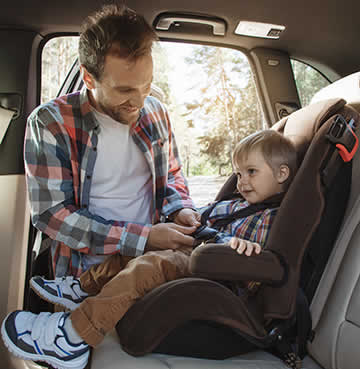 A dad straps his young son into a child's car seat