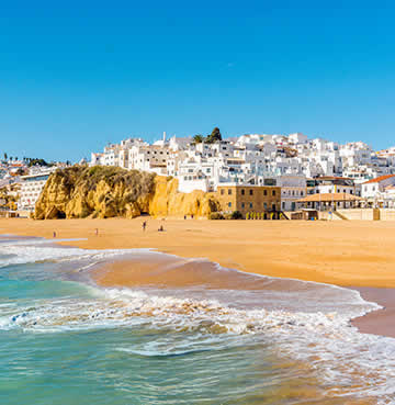Golden sands and crashing waves are overlooked by a whitewashed seaside town in the Algarve