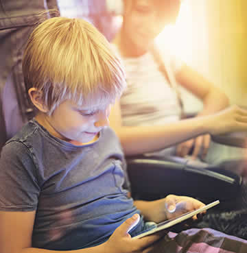Children sit on a plane with their tablets to keep them occupied during the flight