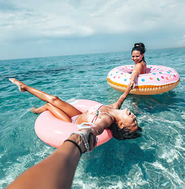 Mother and daughter on doughnut-themed inflatables in the sea on a beach holiday