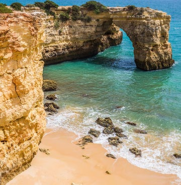 Towering golden cliffs and turquoise sea on an Algarve beach