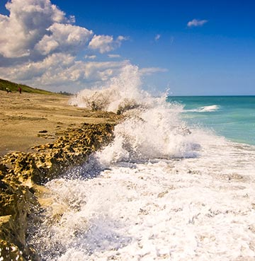 Waves crash against the limestone craggy rocks at Blowing Rocks Preserve in Jupiter, Florida