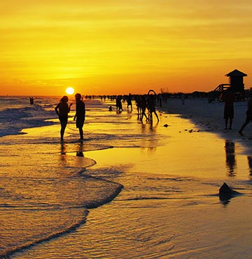 A famous Siesta Key golden sunset. Silhouettes of onlookers admire the colours in the sky from the beach.