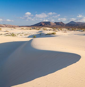 Powder-white sand dunes snake as far as the eye can see. Mountains line the skyline with brilliant blue skies above.
