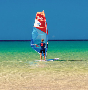 A young windsurfer sets off on calm waters.