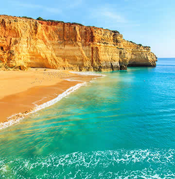 Turquoise sea and golden beaches back by towering cliffs in the Algarve, Portugal