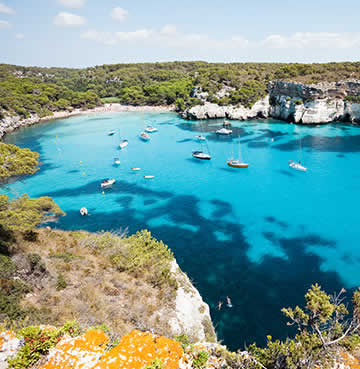 A craggy inlet in Menorca with boats moored for the day