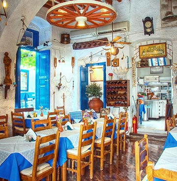 The interior of a traditionally decorated Greek taverna with white walls and blue shutters.