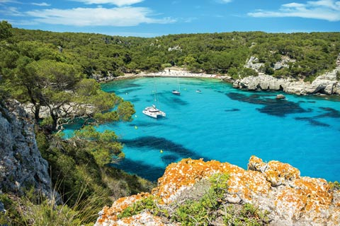 Lush vegetation and rocky headlands shelter the blissful little bay of Cala Macarella, Menorca