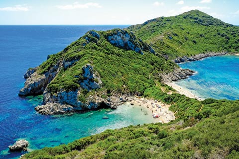 Porto Timoni's twin beaches surrounded by rugged rocky hills covered in trees and azure turquoise waters