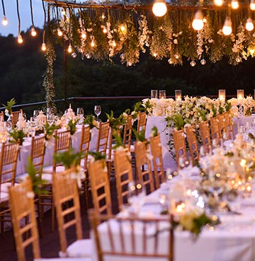 A rustic and romantic wedding breakfast table layout. White linen flows across the tables while flower garlands decorate the middle and festoon lights hang above.