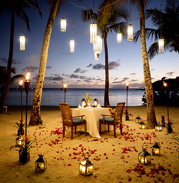 A romantic beach front dinner set-up. Rose petals are scattered across the sand, candles in lanterns surround the table and lights hang in the palm trees above the table. Calm seas lap against the shore.