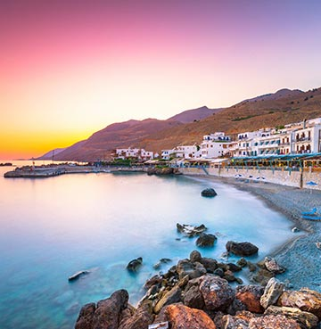 A beautiful romantic coastal sunset in Crete, with a sleepy village nestled at the bottom of a mountainous backdrop
