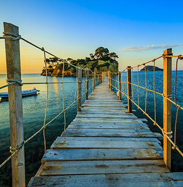 A rustic wooden rope bridge connects mainland Zakynthos to the stunning Cameo Island